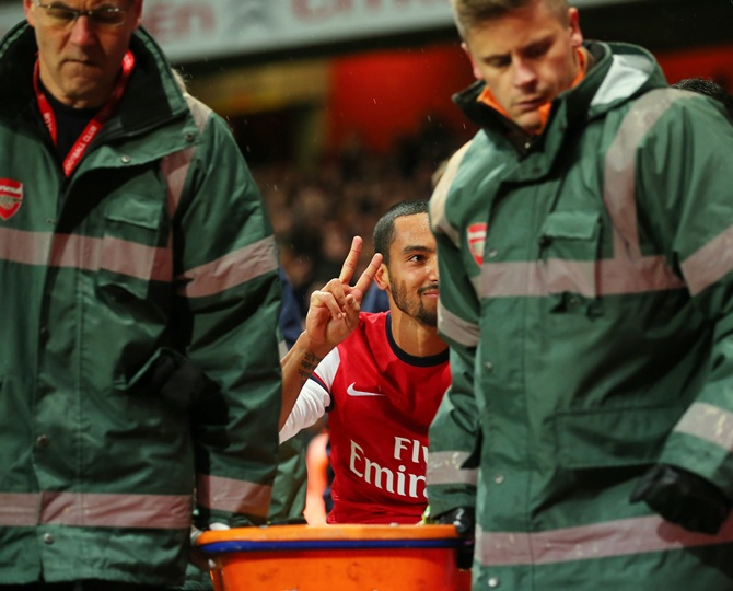 The injured Theo Walcott of Arsenal makes a 2-0 gesture to the Tottenham fans as he is stretchered off the pitch