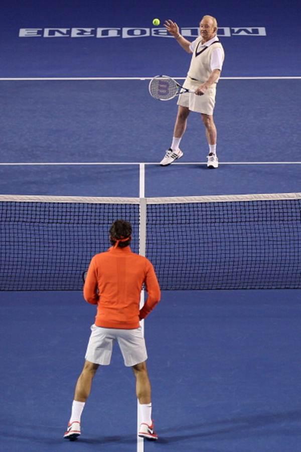 Rod Laver plays a backhand against Roger Federer