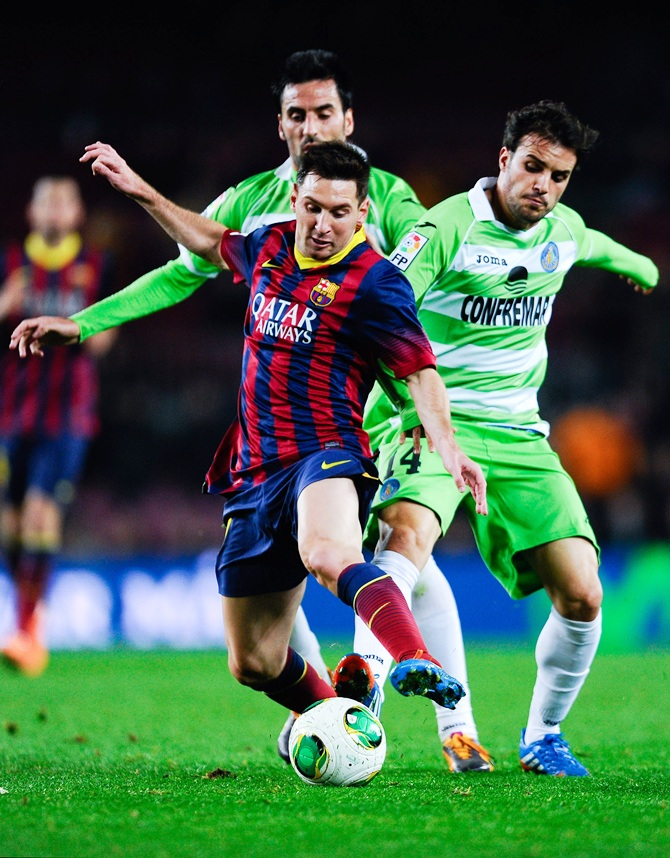 Lionel Messi of FC Barcelona duels for the ball with Juan Rodriguez (left) and Pedro Leon of Getafe CF