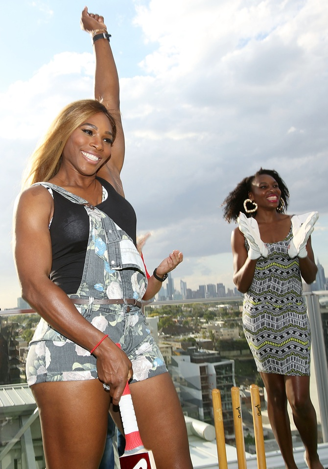 Serena Williams (left) celebrates a shot with sister Venus Williams