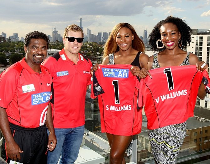 Melbourne Renegades players Muthiah Muralidaran (left) and Aaron Finch (right) pose with Venus Williams and Serena Williams