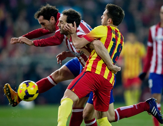Jordi Alba (right) of FC Barcelona holds the ear of Juan Francisco Torres (second left) of Atletico de Madrid as his teammate Diego Godin (left) strikes the ball