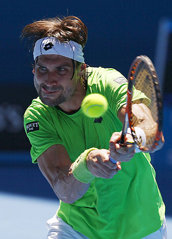 David Ferrer of Spain hits a return to Alejandro Gonzalez of Colombia during their men's singles match at the Australian Open in Melbourne on Monday