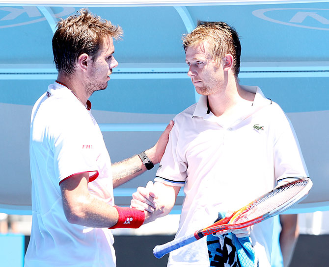 Stanislas Wawrinka of Switzerland greets Andrey Golubev of Kazakhstan after the latter retired during their first round match at the Australian Open at Melbourne Park on Monday