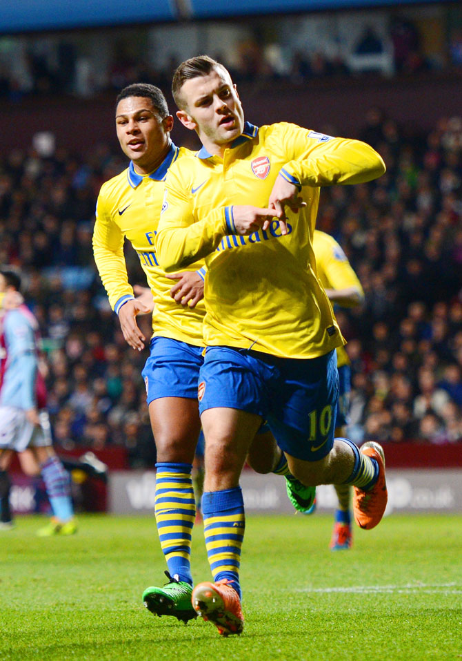 Jack Wilshere of Arsenal celebrates with teammate Serge Gnabry after scoring the opening goal against Aston Villa during their Barclays Premier League match at Villa Park in Birmingham on Monday