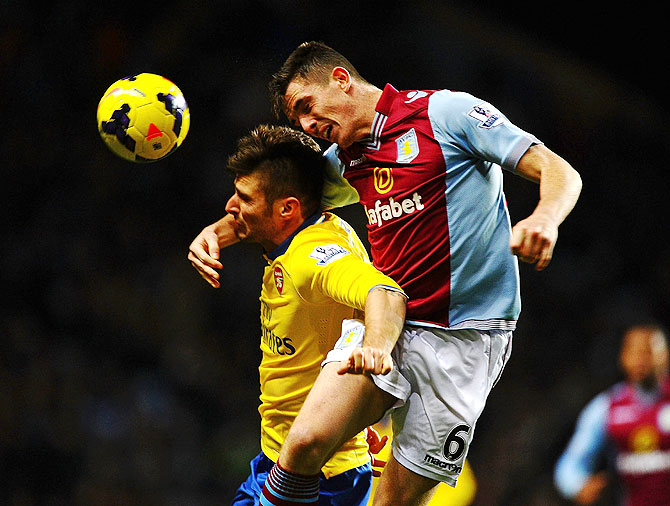 Ciaran Clark of Aston Villa challenges Olivier Giroud of Arsenal during their match on Monday