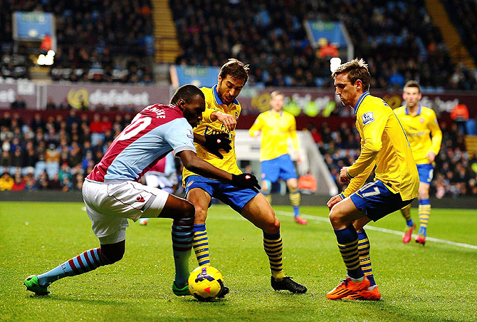 Christian Benteke of Aston Villa (left) is closed down by Mathieu Flamini and Per Mertesacker of Arsenal during their English Premier League match on Monday