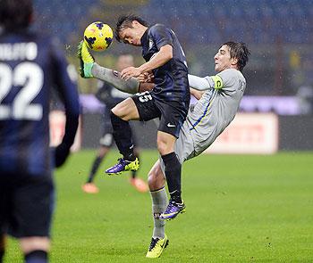 Yuto Nagatomo of Inter Milan (left) and Simone Bentivoglio of AC Chievo Verona vie for the ball during their Serie A match at San Siro Stadium in Milan on Monday
