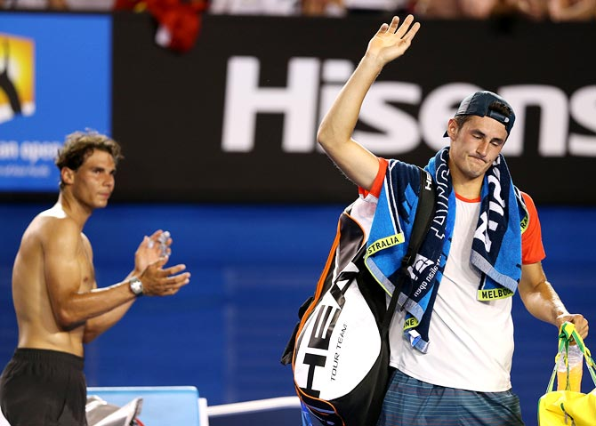 Bernard Tomic (right) leaves the court as Rafael Nadal claps