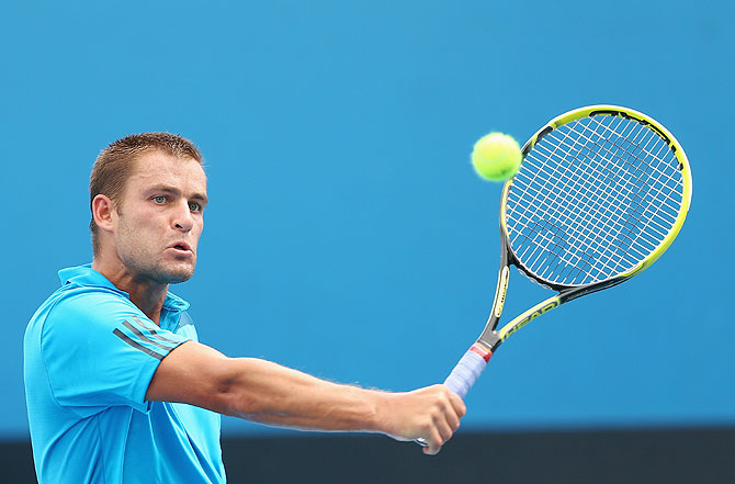 Mikhail Youzhny of Russia plays a backhand in his second round match against Florian Mayer of Germany at the Australian Open at Melbourne Park on Wednesday