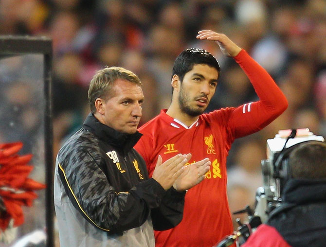 Liverpool FC Manager Brendan Rodgers (left) looks on as Luis Suarez is substituted