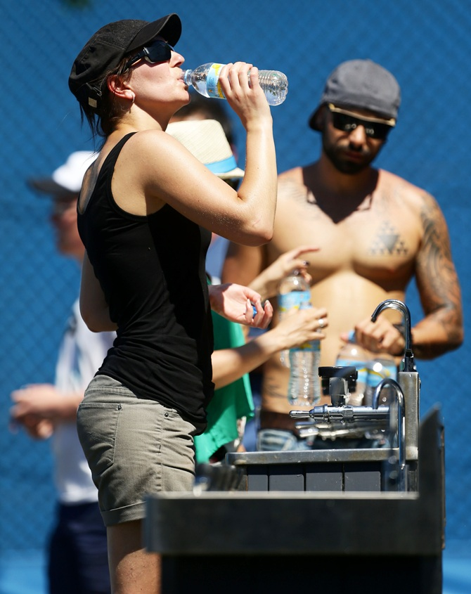 A tennis fan cools off at a water fountain as Melbourne heads towards 43 degrees celsius (109 degrees fahrenheit)   during day two of the 2014 Australian Open at Melbourne Park