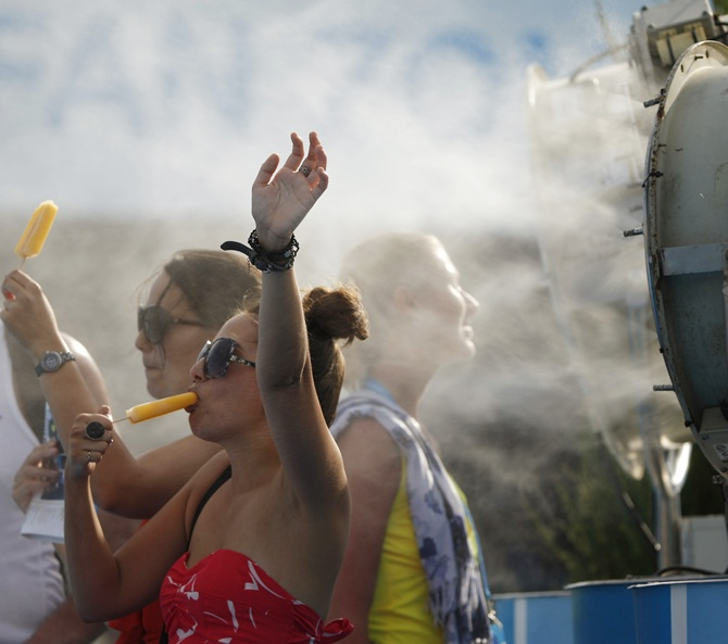 Spectators cool off with popsicles in front of a misting fan at the Australian Open in Melbourne