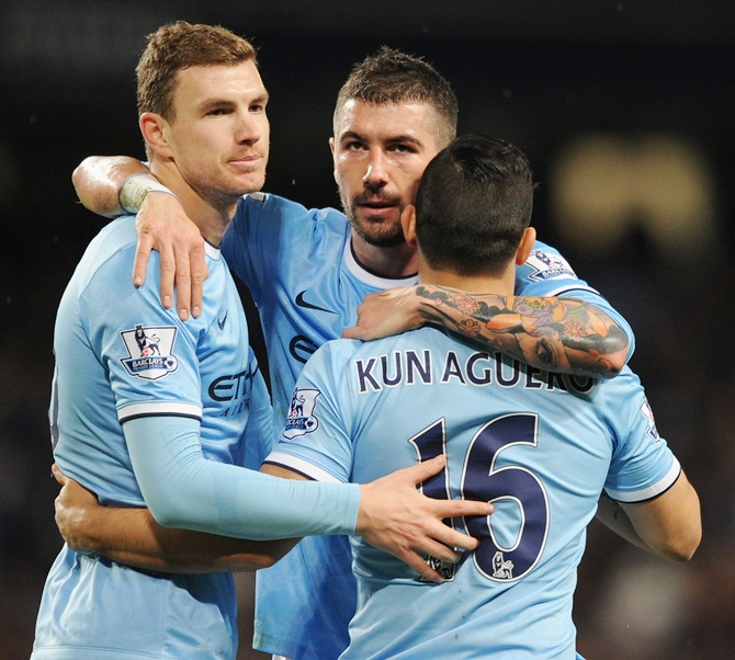 Sergio Aguero of Manchester City celebrates scoring his team's fourth goal with team-mates Edin Dzeko (left) and Aleksandar Kolarov