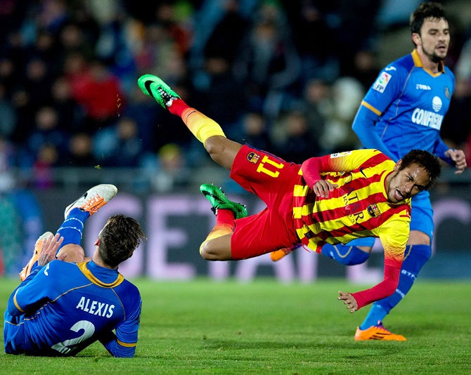 Neymar of FC Barcelona is tackled by Alexis Ruano of Getafe