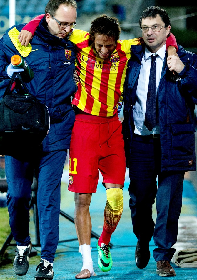 Neymar of Barcelona is assisted as he leaves the pitch after picking up an injury