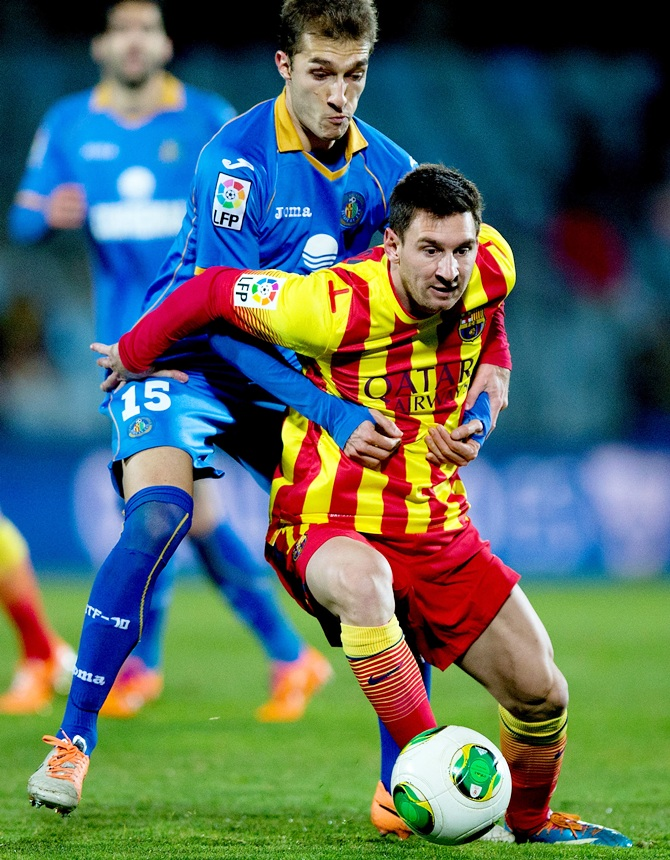 Lionel Messi of FC Barcelona competes for the ball with Rafael Lopez of Getafe