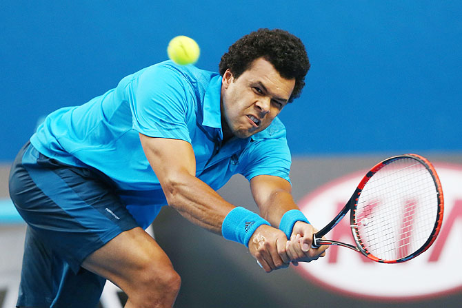Jo-Wilfried Tsonga of France plays a backhand in his third round match against compatriot Gilles Simon on Saturday