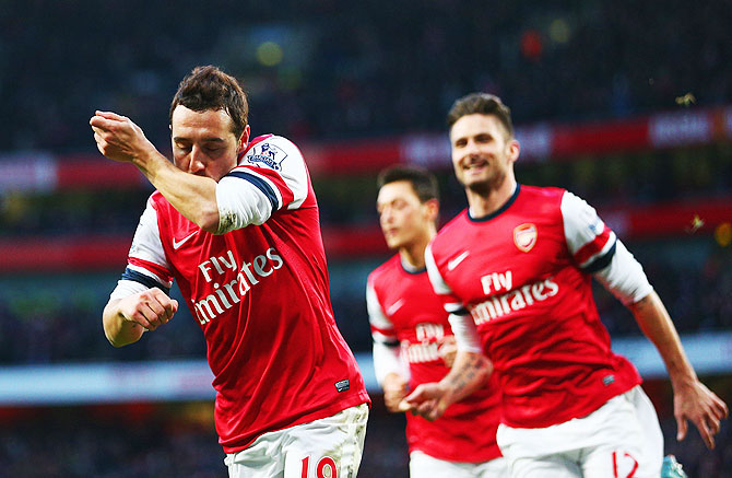 Santi Cazorla of Arsenal (left) celebrates with Olivier Giroud (right) after scoring against Fulham at Emirates Stadium in London on Saturday