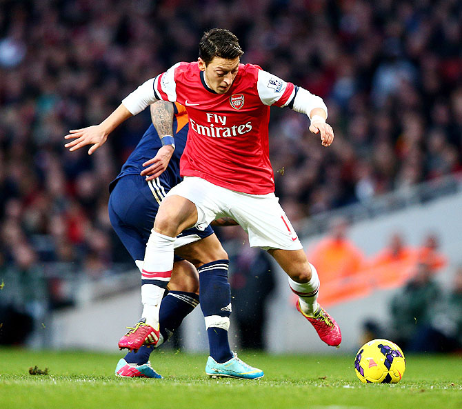 Mesut Ozil of Arsenal is challenged by Ashkan Dejagah of Fulham during their match on Saturday