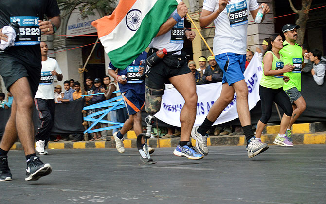 A runner with an amputated leg runs with the India flag