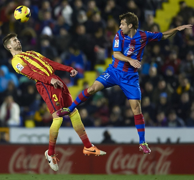 Andreas Ivanschitz (right) of Levante competes for the ball with Gerard Pique of Barcelona