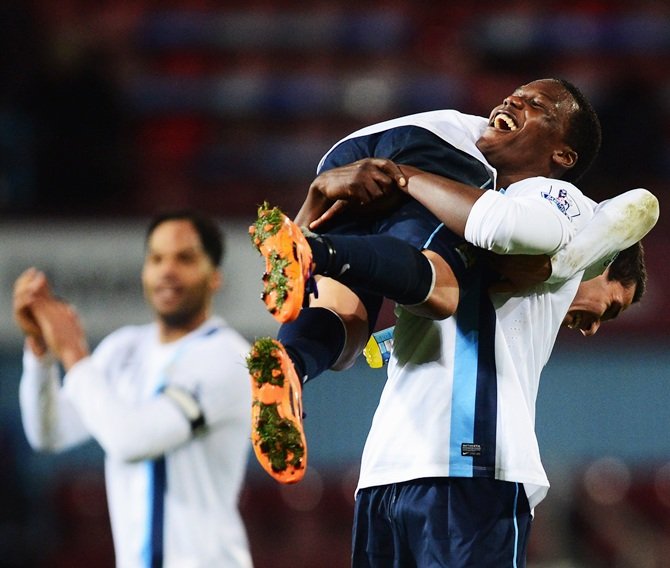 Dedryck Boyata of Manchester City lifts team mate Marcos Mesquita Lopes in celebration after victory