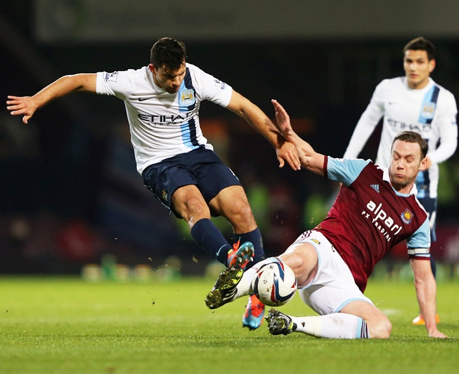 Sergio Aguero of Manchester City is tackled by Kevin Nolan of West Ham United