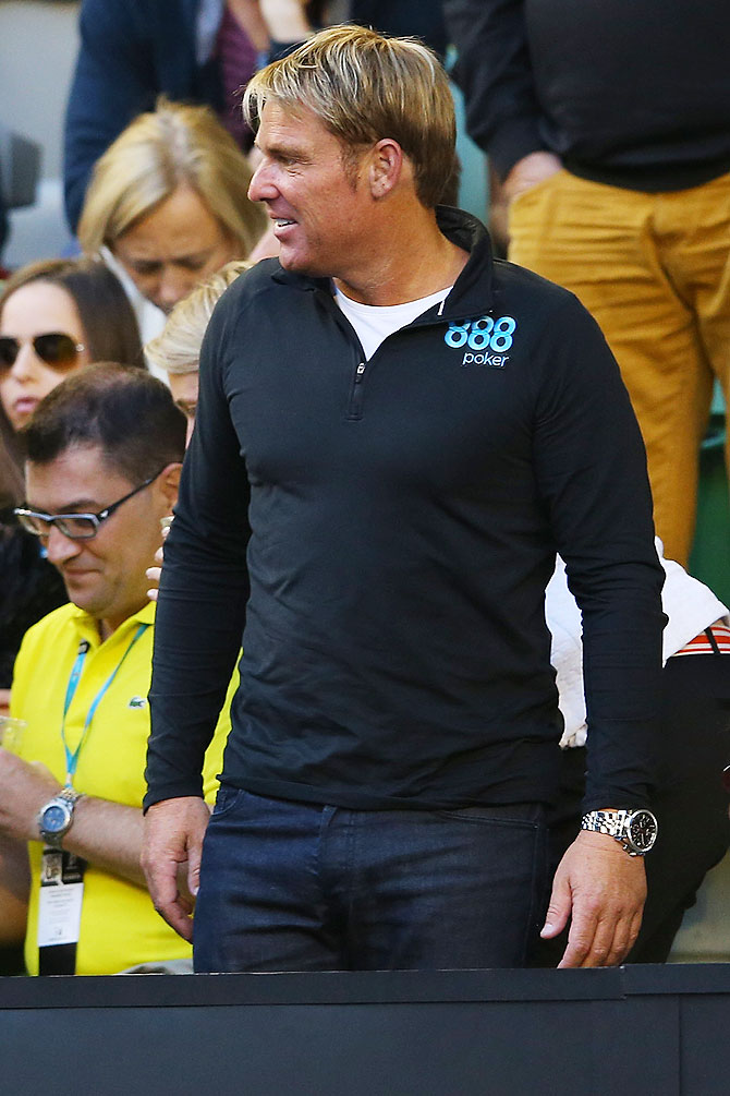 Former Australian cricketer Shane Warne watches the quarter-final between Roger Federer and Andy Murray