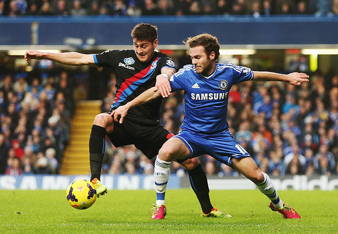 Joel Ward of Crystal Palace and Juan Mata of Chelsea challenge for the ball during the Barclays Premier League match