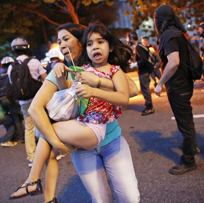 A woman carries her daughter away from their car, after it caught fire   driving through a flaming barrier during a protest against the 2014 World Cup in Sao Paulo