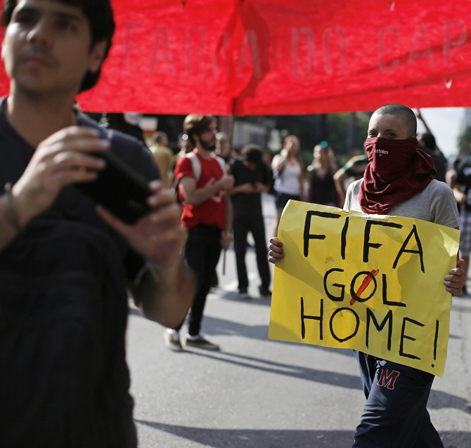 A demonstrator holds a banner during a protest against the 2014 World Cup in Sao Paulo