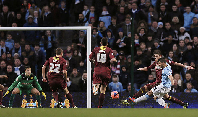 Manchester City's Sergio Aguero (right) scores his second goal against Watford during their English FA Cup fourth round match at the Etihad Stadium in Manchester on Saturday