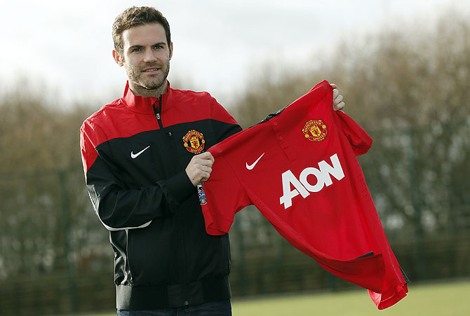 Manchester United's new signing Juan Mata holds a club shirt during a photocall at the club's Carrington training complex in Manchester on Monday