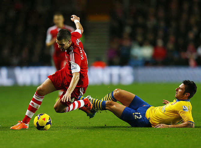 Arsenal's Olivier Giroud (right) fouls Southampton's Morgan Schneiderlin during their English Premier League match at St.Mary's Stadium in Southampton on Tuesday
