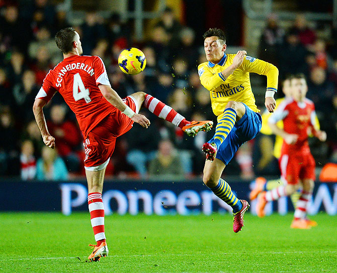 Morgan Schneiderlin of Southampton and Mesut Oezil of Arsenal vie for possession