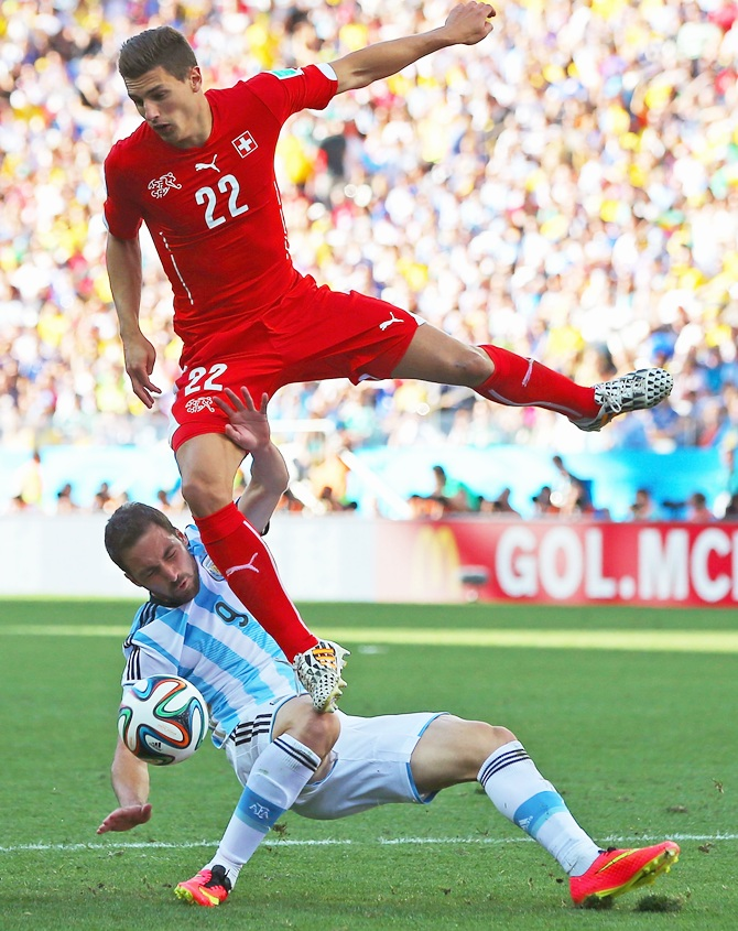 Fabian Schar of Switzerland collides with Gonzalo Higuain of Argentina