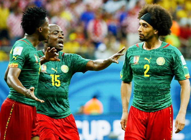 Cameroon's Achille Weboc ,centre, tries to separate teammates Benjamin Moukandjo, left, and Benoit Assou-Ekotto as they argue during their Group A match against Croatia