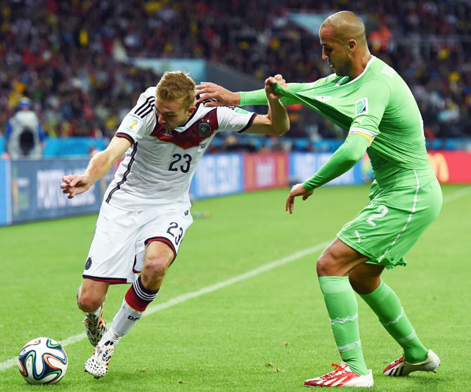 Christoph Kramer of Germany controls the ball against Madjid Bougherra of Algeria during their match on Monday