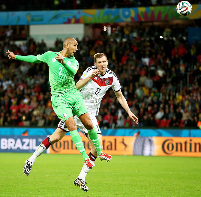 Madjid Bougherra of Algeria and Per Mertesacker of Germany are involved in an aerial challenge during their match on Monday