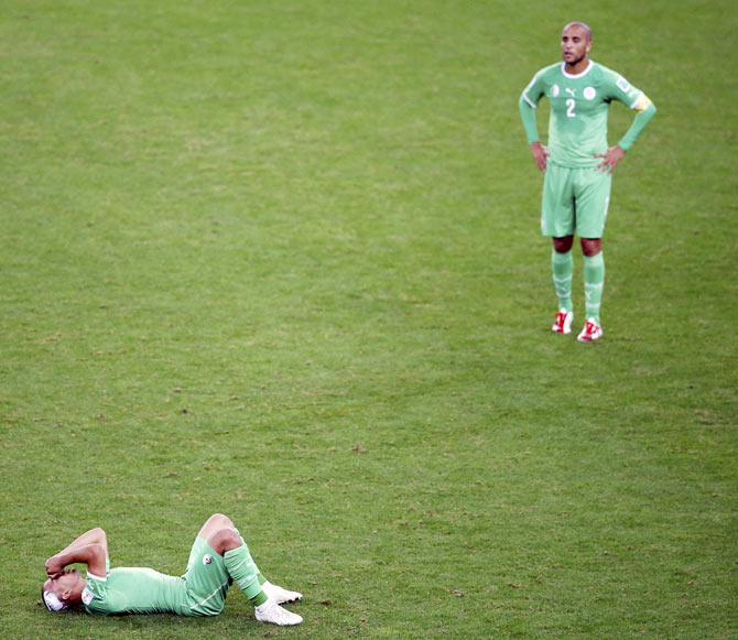 Algeria's Sofiane Feghouli and Madjid Bougherra react after their 2014 World Cup round of 16 game against Germany on Monday