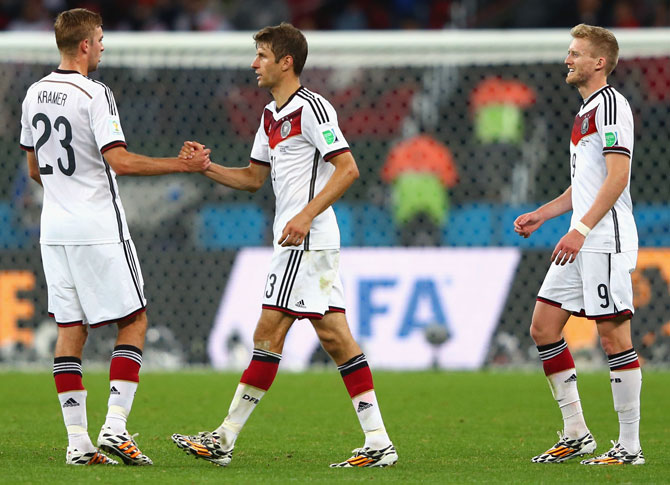 (left to right) Christoph Kramer, Thomas Mueller, Andre Schuerrle of Germany celebrate after defeating Algeria 2-1