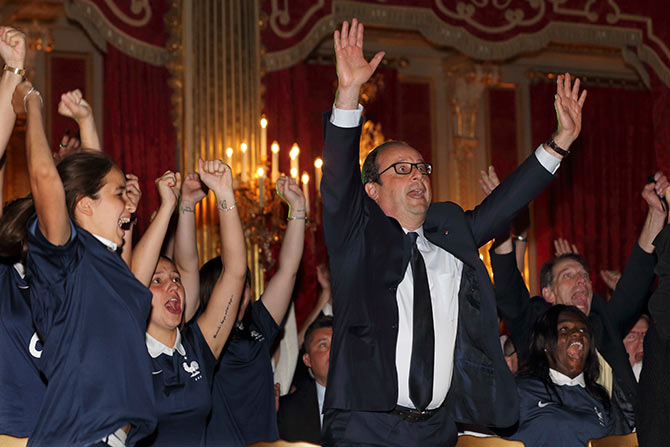 French President Francois Hollande (right) celebrates as France team scores a goal against Nigeria in their 2014 World Cup round of 16 game