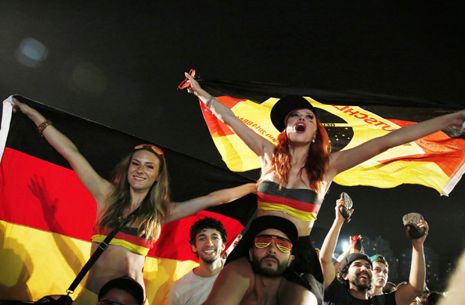 German soccer fans celebrate at the end of the match against Algeria during a broadcast at Copacabana beach in Rio de Janeiro