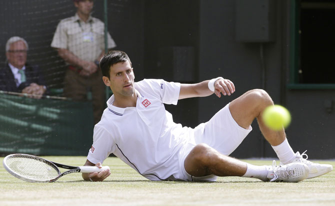 Novak Djokovic of Serbia slips during his quarter-final against Marin Cilic of Croatia at the Wimbledon