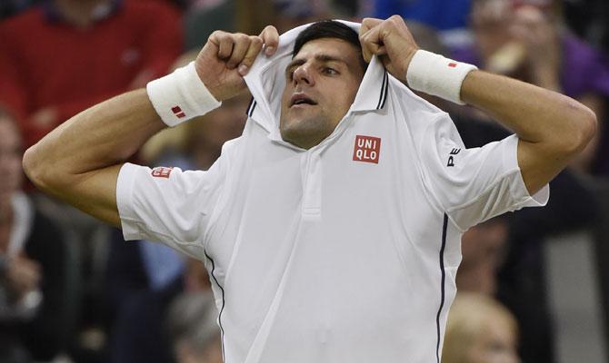 Novak Djokovic of Serbia takes off his shirt during a break