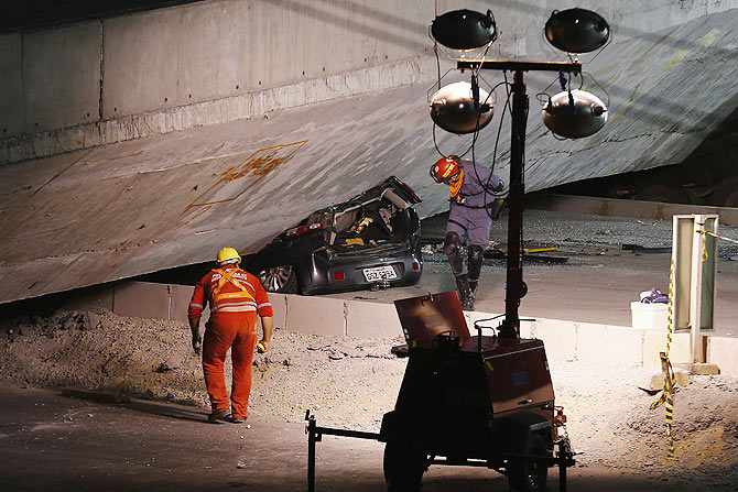 Rescue workers inspect a car trapped underneath a bridge that collapsed while under construction in Belo Horizonte on Thursday