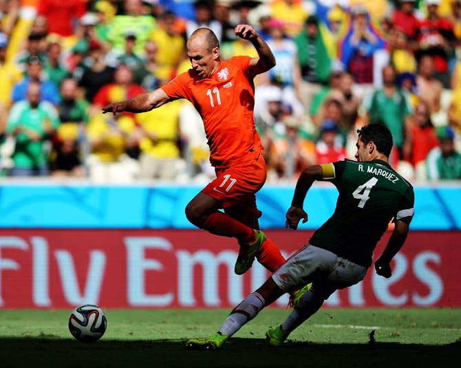 Arjen Robben of the Netherlands tries to get the ball past Mexico's Rafael Marquez