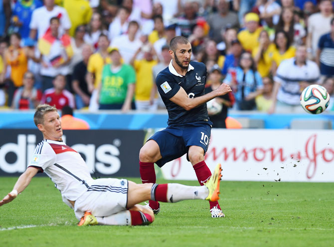 Bastian Schweinsteiger of Germany tackles Karim Benzema