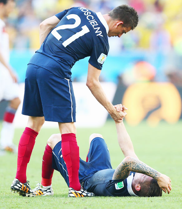 France's Laurent Koscielny (left) consoles teammate Mathieu Debuchy after being defeated by Germany